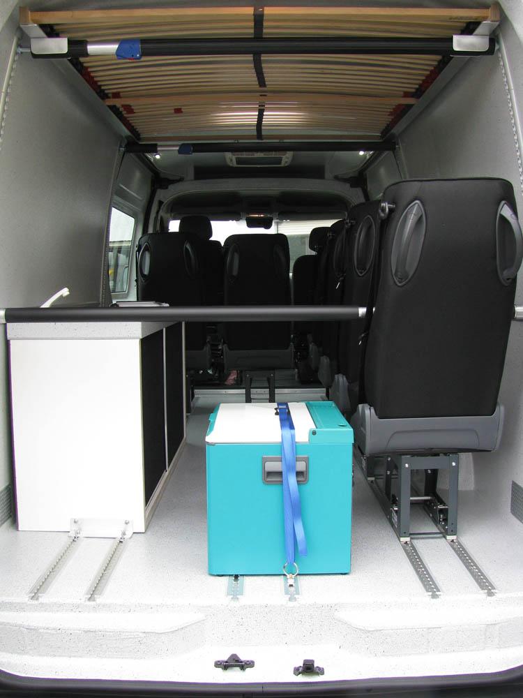 Freizeitmobil ausgestattet mit Bett, Einzelsitzen, Fenstern in den Türen und einer Klimaanlage